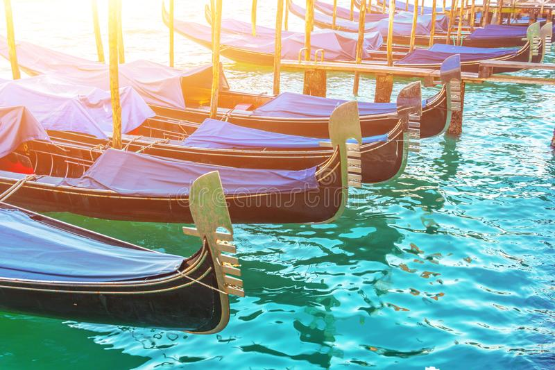Ett antal gondoler på pir i vattnet, fartygparkering Venedig vykortbegrepp royaltyfri bild