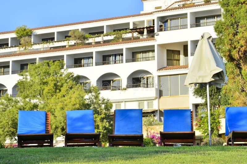 Ett antal soldagdrivare på den gröna gräsmattan framme av hotellet på Coral Beach Hotel Resort Cyprus i Juni 2017 i Cypern royaltyfri bild