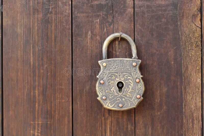 Ett antikt dörrlås och en brun trävägg fotografering för bildbyråer