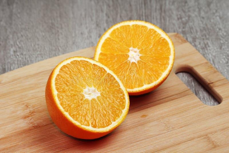 Ett apelsinsnitt in i två halvor royaltyfri foto
