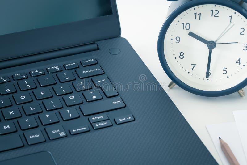 Ett arbetsskrivbord med en dator och kontorstillbehör och en ringklocka som mäter tiden som bort kör Begreppet av akut deadl arkivfoto