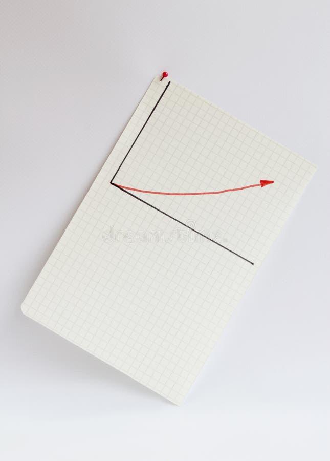 Ett ark av papper i cellen som klämmas fast på en ljus bakgrund På det utdragna diagrammet för ark med en röd pil upp arkivbild