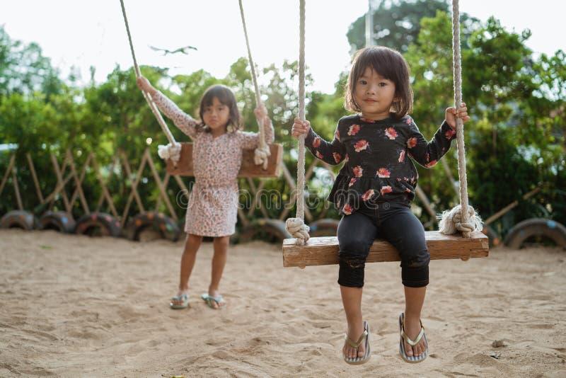 Ett asiatiskt barn för gullig framsida, när spela en gunga med hennes syster arkivfoto