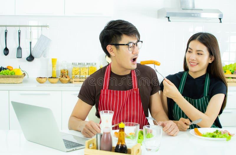 Ett asiatiskt par som har frukosten i köket arkivbild