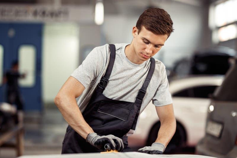 Ett attraktivt automechanic polerar en bil på hans arbete Bilservice och underhåll royaltyfri foto