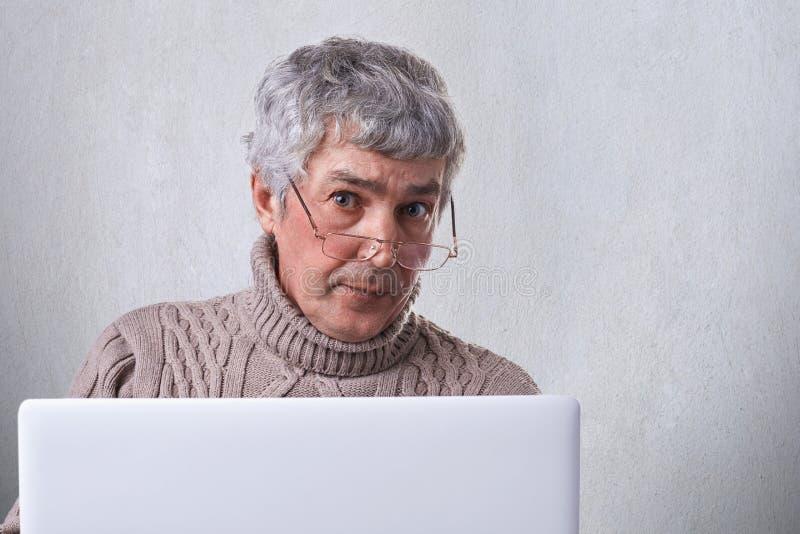 Ett bärande exponeringsglasarbete för säker mogen affärsman med en bärbar dator, medan vara hemmastatt se in i kamera med allvarl royaltyfri bild