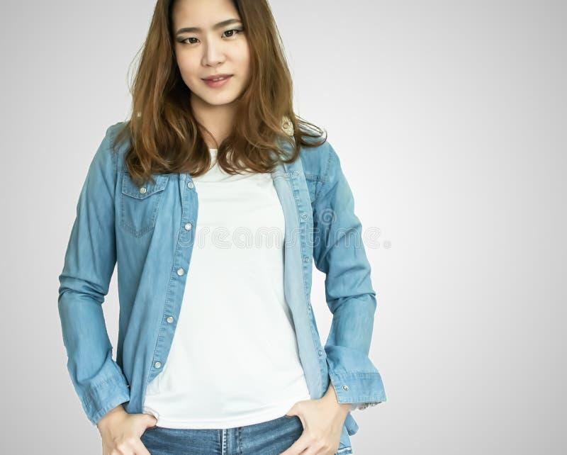 Ett bärande jeanomslag för asiatisk kvinna på vit bakgrund arkivbild