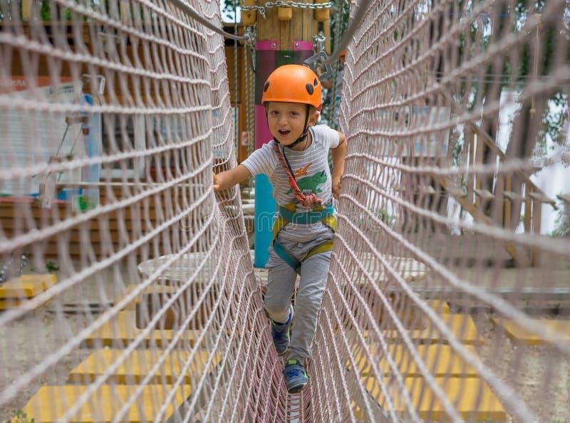 Ett band för vaggaklättrare per fnuren på ett rep En person förbereder sig för stigningen Barnet lär att binda en fnuren Kontroll arkivfoton