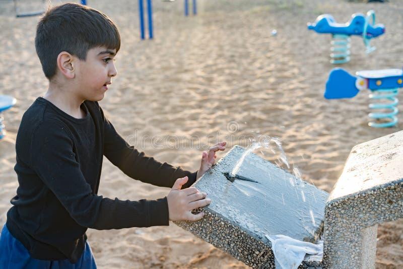 Ett barn använder ett smutsigt vattenklapp royaltyfria foton
