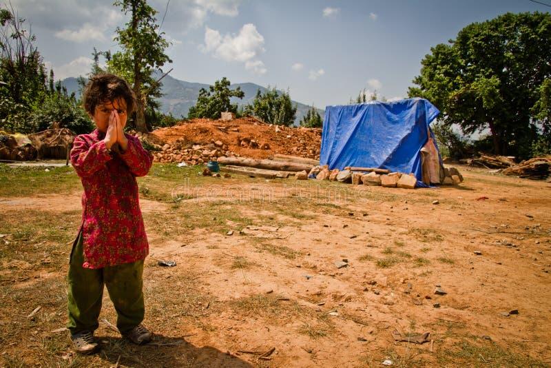 Ett barn av den Chhaimale byn i framdel av henne skövlade hem- afte royaltyfri bild