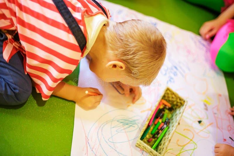 Ett barn drar med färgpennor på papper royaltyfri fotografi