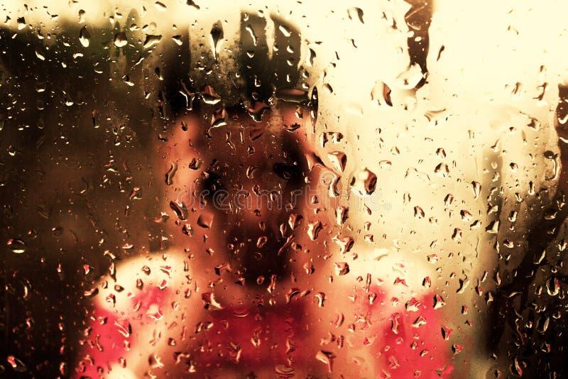 Ett barn håller ögonen på bak exponeringsglas bänkgreen inget regna tabelltree royaltyfri fotografi