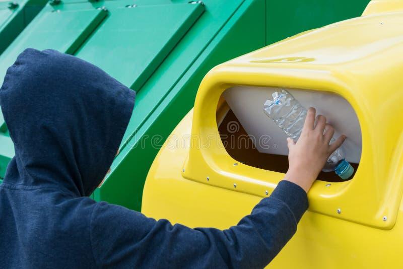 Ett barn i huven kastar en tomglas i en gul behållare påtänkt för plast- avfalls royaltyfri fotografi