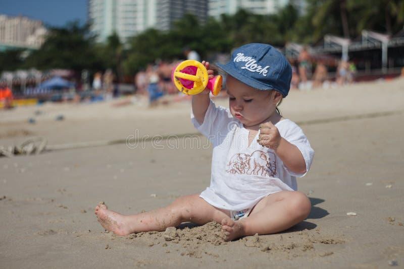 Ett barn i sol-skyddande kläder och en huvudbonad spelar på en sandig strand på en klar varm dag royaltyfri bild
