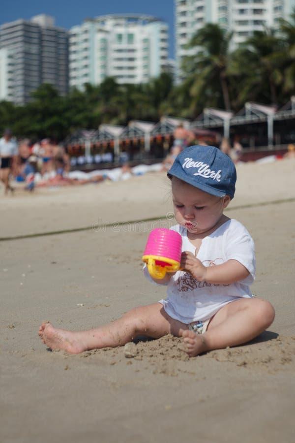 Ett barn i sol-skyddande kläder och en huvudbonad spelar på en sandig strand på en klar varm dag, vertikalt foto arkivbild