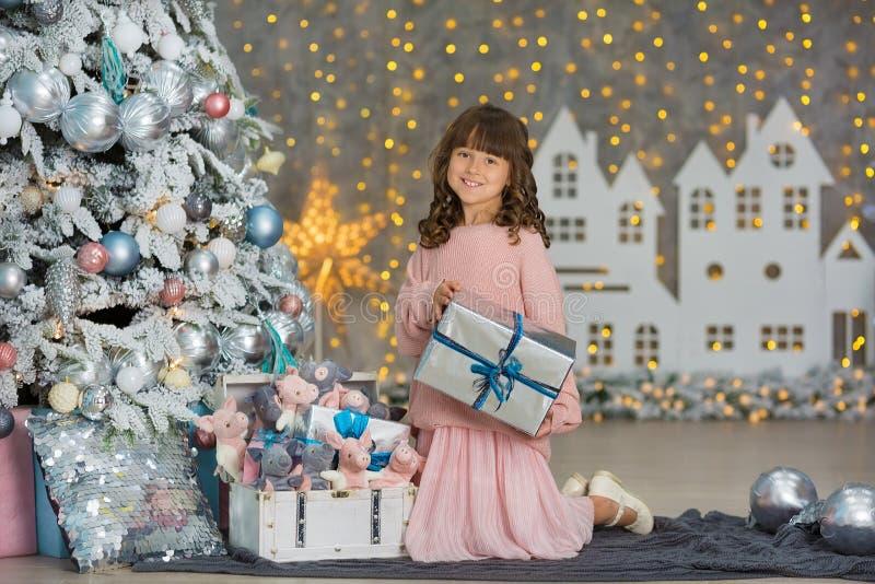 Ett barn i studion för det nya året Flicka i en julfotoperiod festlig mood Vänta på ett mirakel i födelsen royaltyfri bild