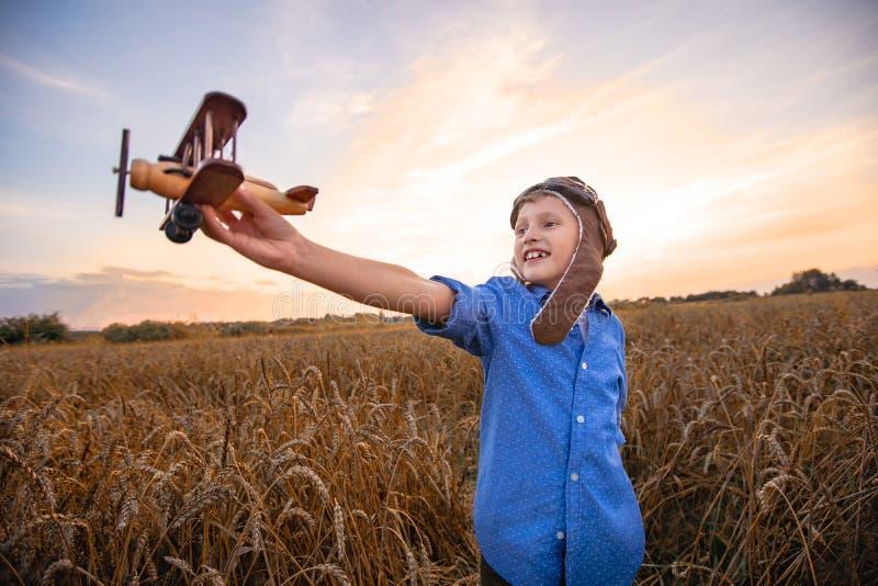 Ett barn i ett vetefält i byn med en retro nivå i hans händer Pojkedr?mmarna av att bli en pilot H?rlig himmel f?r afton royaltyfri foto