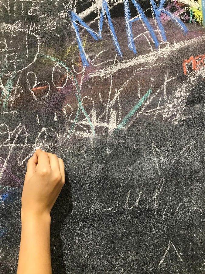 Ett barn målar vid krita på en skolförvaltning royaltyfri fotografi