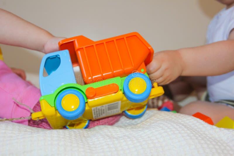 Ett barn och en färgrik skrivmaskin Barn tar leksaken från ea royaltyfri foto
