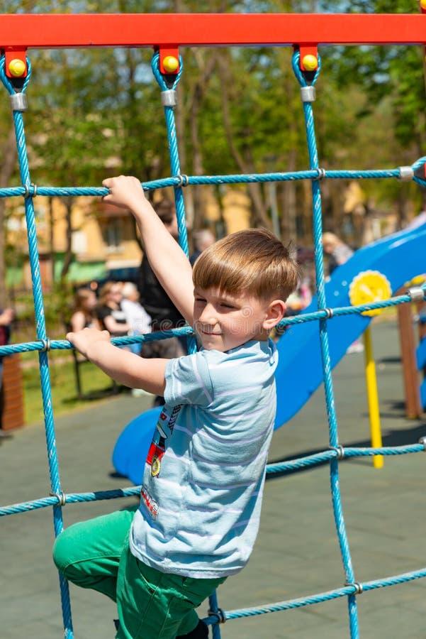 Ett barn på sportlekplatsen, en pojke klättrar kabelbilen, och klättringar till överkanten i en ytterlighet parkerar royaltyfria foton