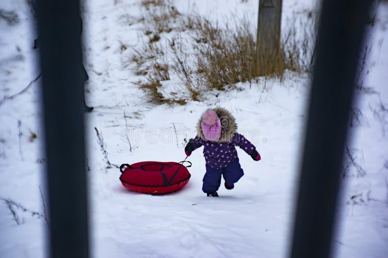 Ett barn rider en ostkaka med en snöig kulle arkivfoton
