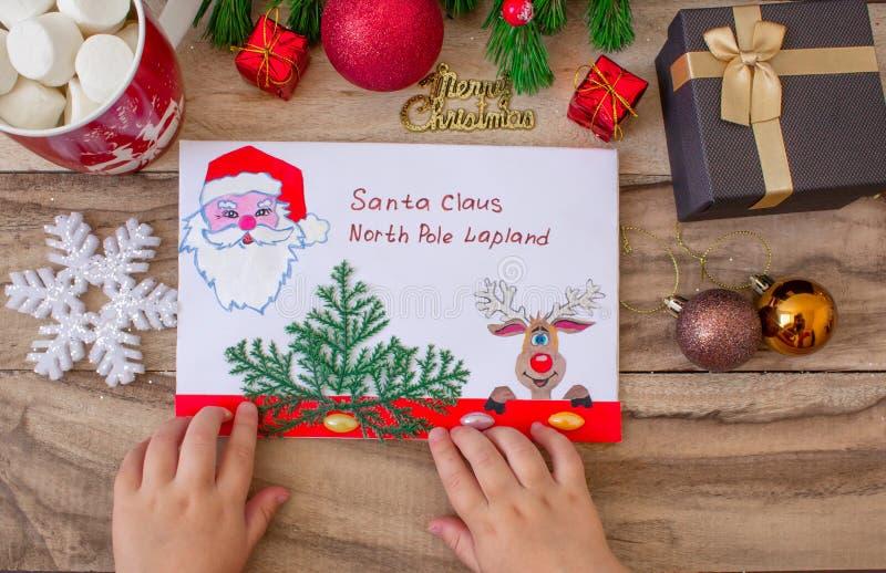 Ett barn rymmer en bokstav till Santa Claus på nordpolen i Lapland, barns händer på en träbakgrund med garneringar och C royaltyfri foto