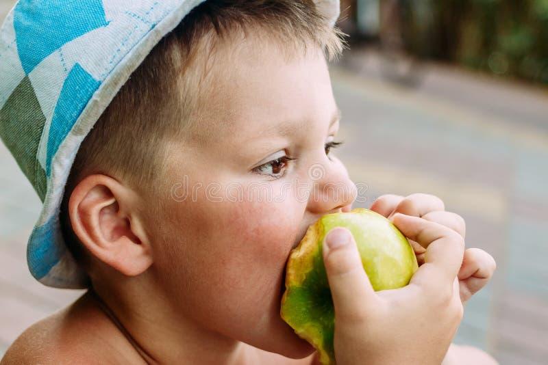 Ett barn som bitas av en gröna Apple royaltyfria bilder