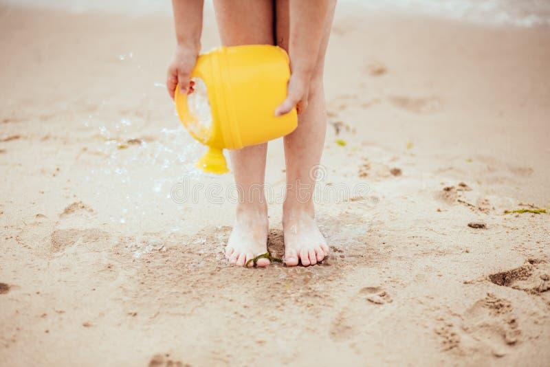 Ett barn spelar på stranden Vattenkörningar till sanden från bevattna kan arkivbilder