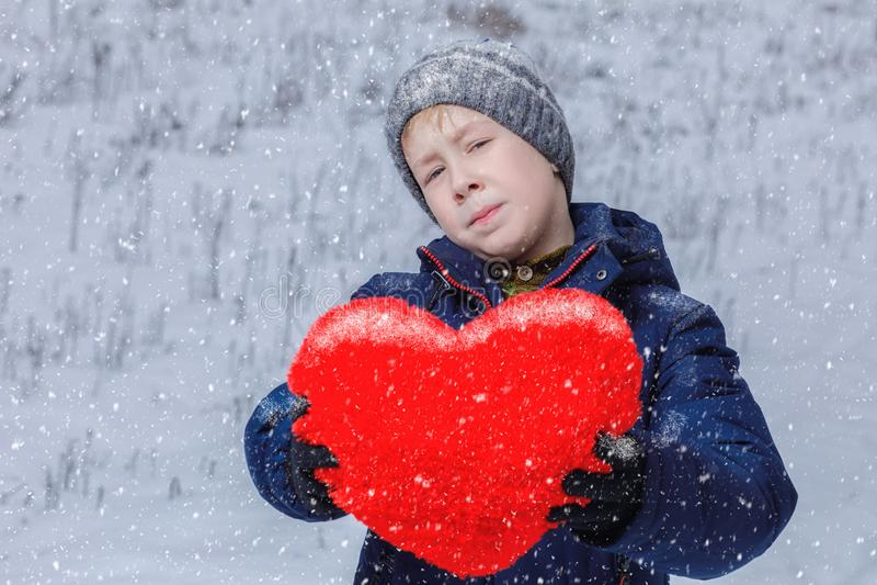 Ett barn visar en hjärta i hans händer royaltyfri foto