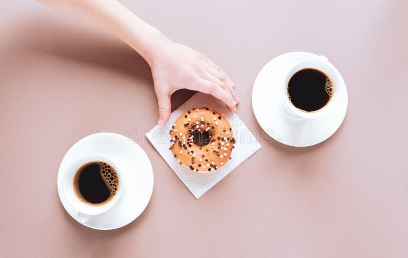 Ett barns hand tar en smaklig hand. två koppar kaffe arkivfoton