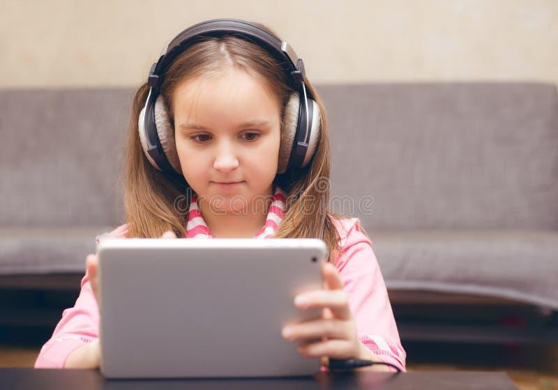 Ett barnsammanträde på en tabell i det stort och blickar på datoren royaltyfria bilder