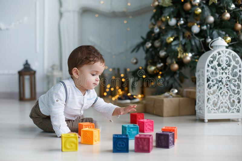 Ett barnsammanträde på golvet nära en smart julgran som spelar med kulöra kuber arkivfoton