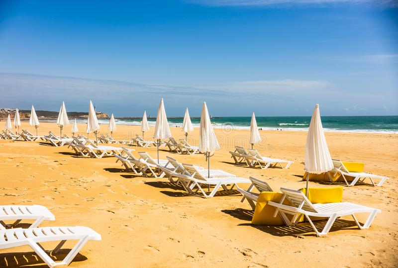 Ett bedöva havshavlandskap med sunbeds och paraplyer i Portimao, Portugal Algarve region arkivbilder