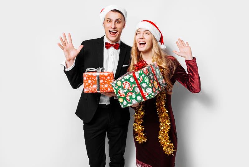 Ett bedövat par av vänner i Santa Claus hattar som firar det nytt royaltyfri fotografi