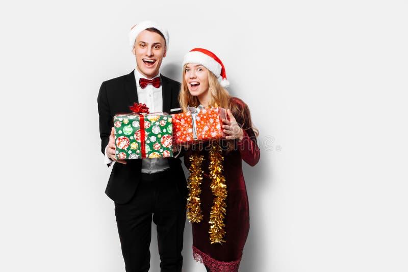 Ett bedövat par av vänner i Santa Claus hattar som firar det nytt arkivfoton