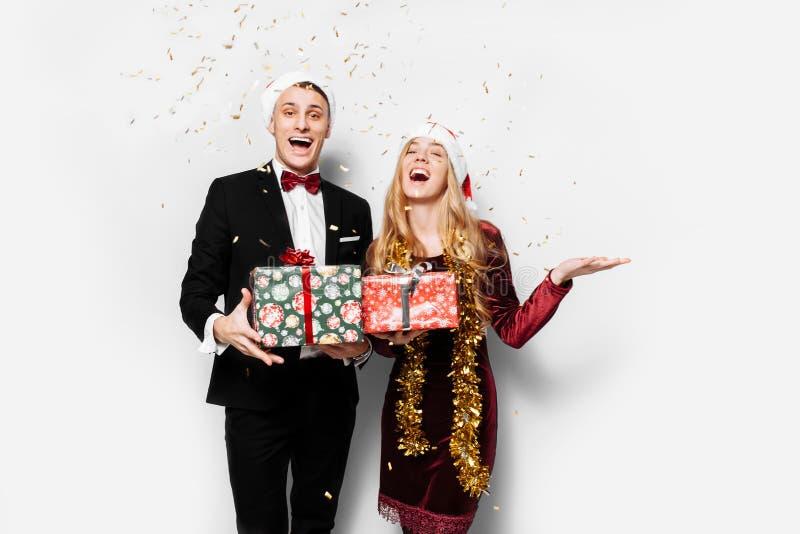 Ett bedövat par av vänner i Santa Claus hattar som firar det nytt royaltyfri foto