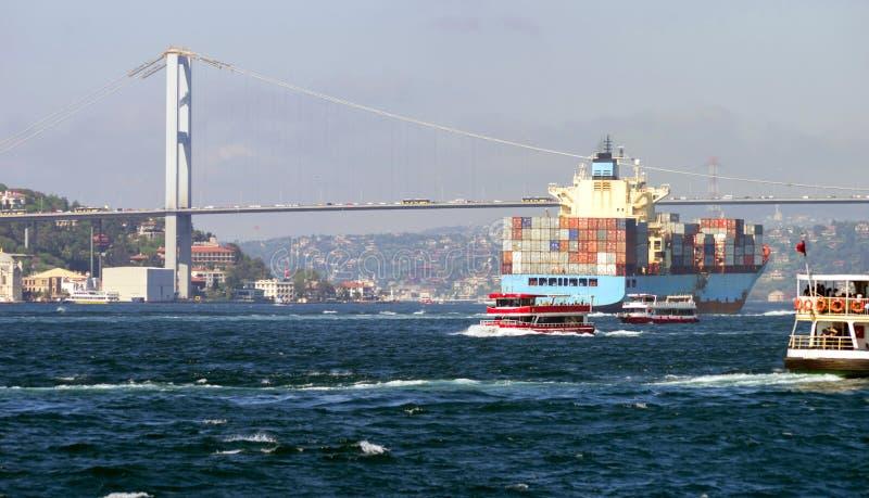 Ett behållareskepp och flera små passagerareskepp nära 15 den Juli martyrbron på Bosphorusen arkivfoto