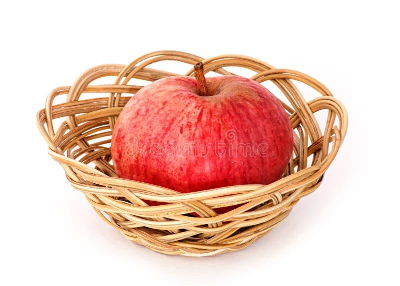 Ett bigred äpple i korgen royaltyfri foto