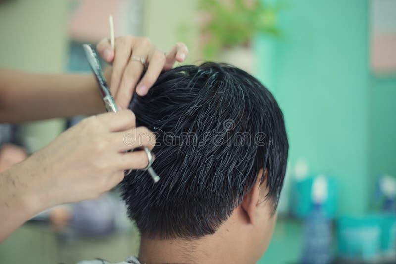 Ett bitande hår för man på barberaren royaltyfri fotografi