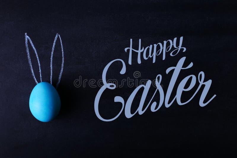 Ett blått målat påskägg på en svart tavla med pressande öron ser som en kanin Text lyckliga easter royaltyfri bild