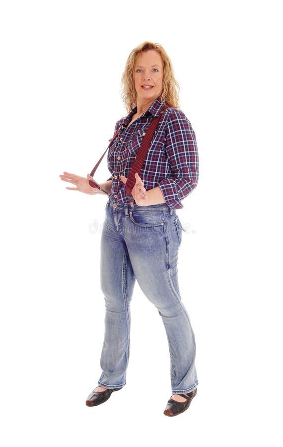 Ett blont kvinnaanseende i jeans och suspender arkivbild