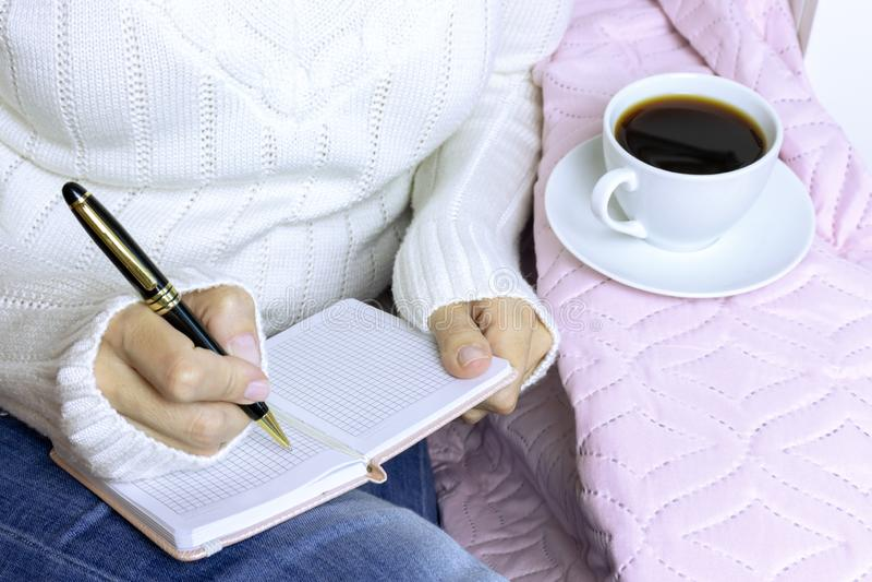 Ett blont kvinnasammanträde på den vita soffan med en kopp kaffe och en handstil i stadsplanerare arkivbilder