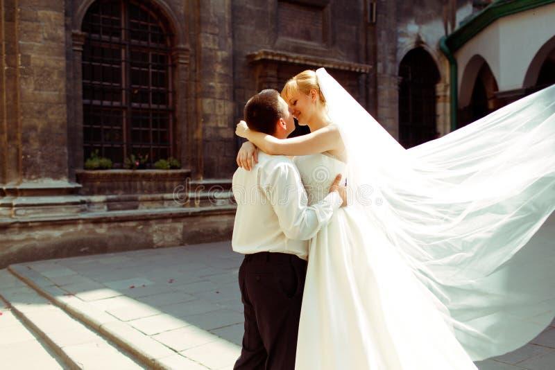 Ett brölloppar kysser i ljusen av den stående behien för morgonsolen royaltyfri foto
