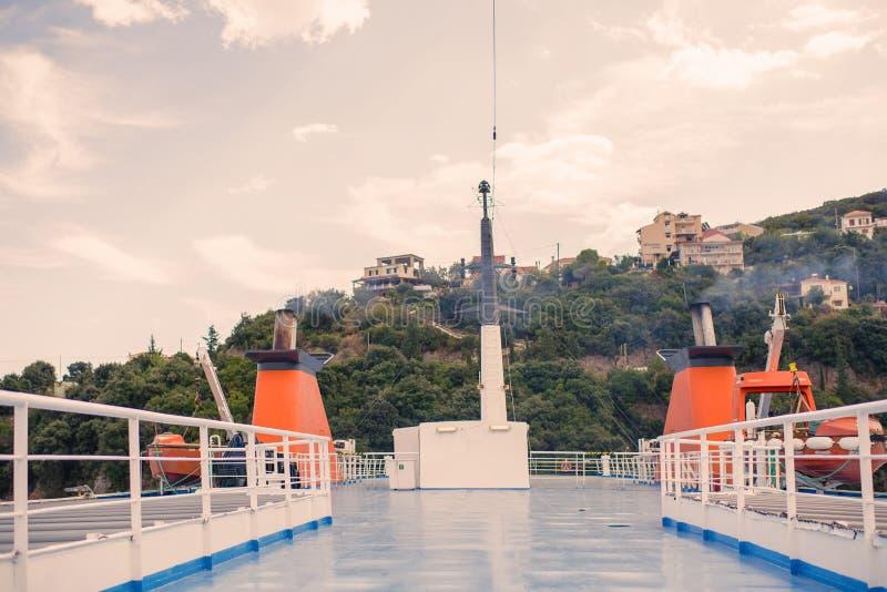 Ett däck för öppen luft med två röda metalliska rör och navigeringantenner på en bakgrund för by och för molnig himmel royaltyfria foton