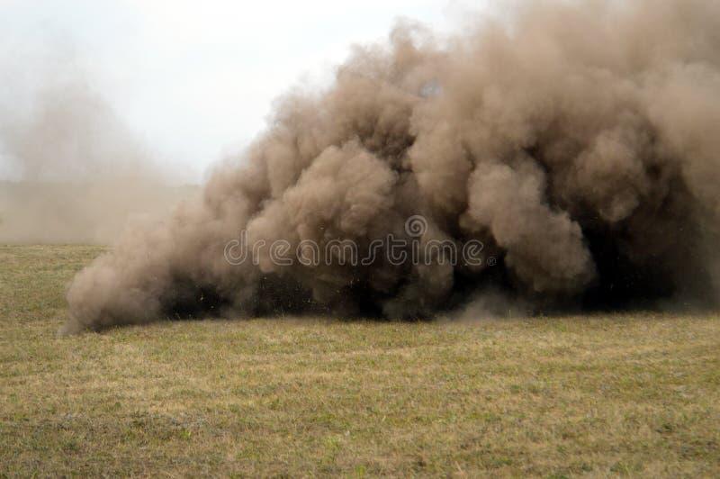 Ett dammmoln bildar tromben på ett lantgårdfält royaltyfri fotografi