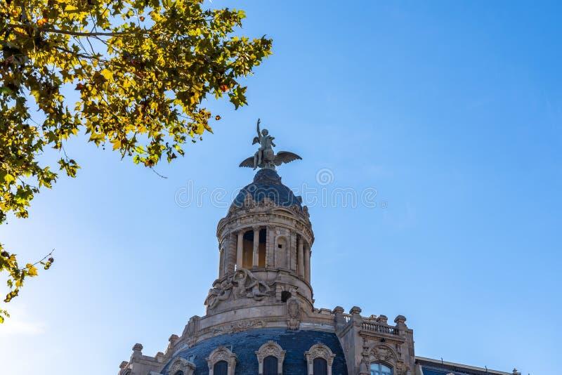 Ett diagram med en bevingad fågel att sitta uppe på en kupol upptill av en byggnad på Passeig de Gracia i Barcelona fotografering för bildbyråer