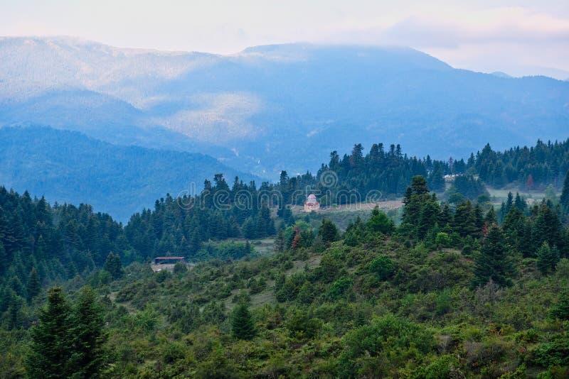 Ett dimmigt grekiskt berglandskap med den lilla kyrkan arkivbilder