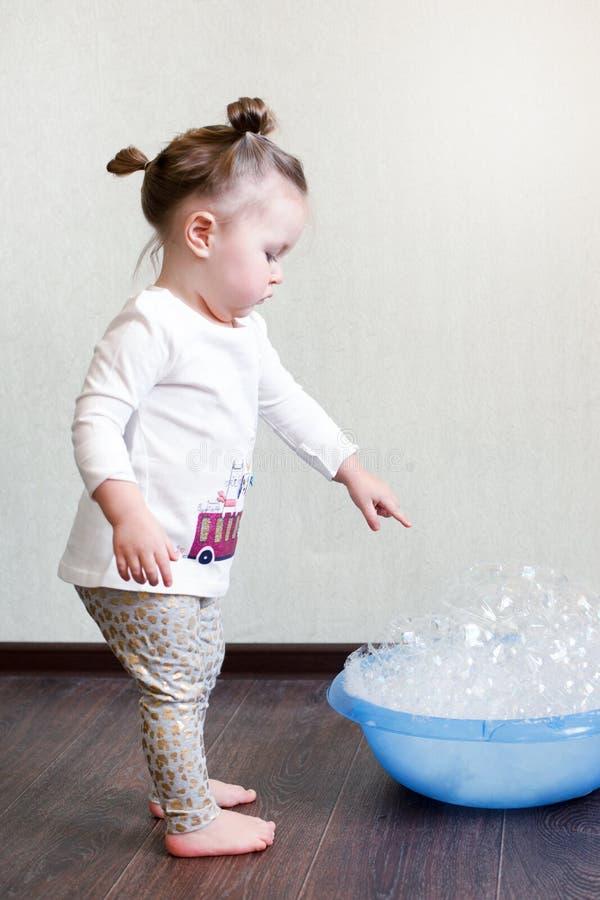 Ett drev för hårddisk 1,8 den 5-åriga flickan är förlovad i hushållsysslor, studerar en handfat med skum, kemisk kemi Hushållruti arkivbilder