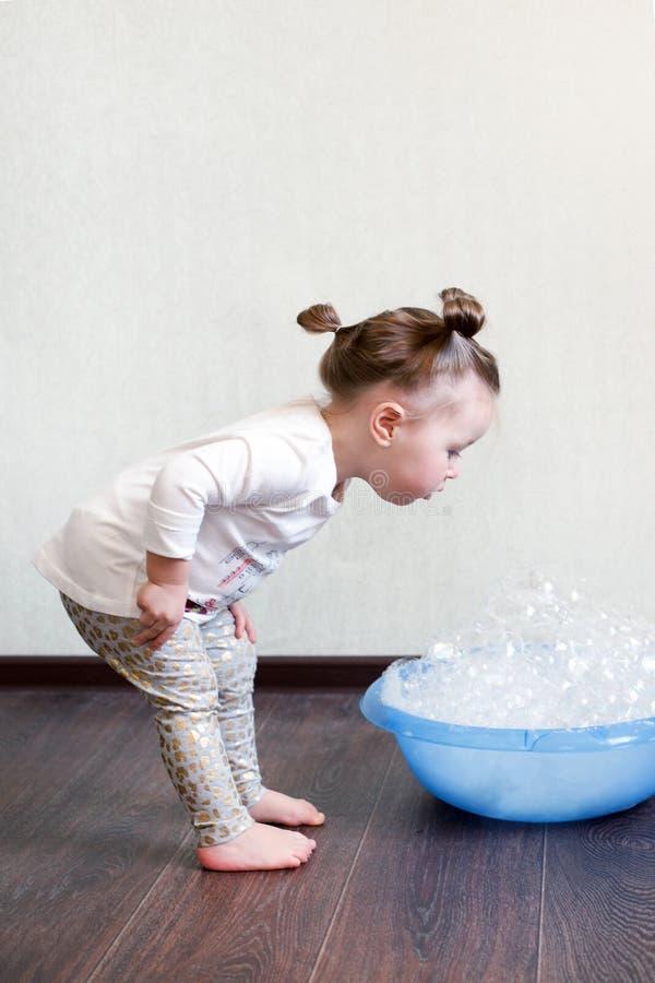 Ett drev för hårddisk 1,8 den 5-åriga flickan är förlovad i hushållsysslor, studerar en handfat med skum, kemisk kemi Hushållruti fotografering för bildbyråer