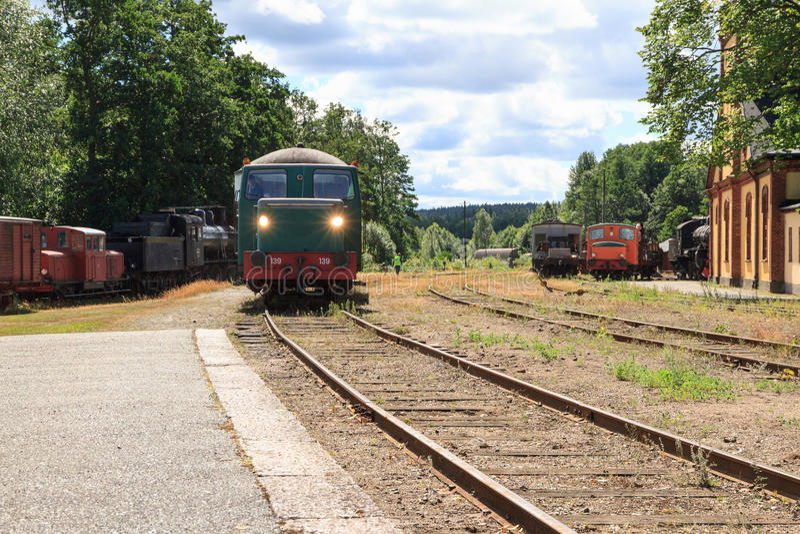 Ett drev som drar in i den gamla drevstationen på sjökusten i Nora Sweden royaltyfri bild